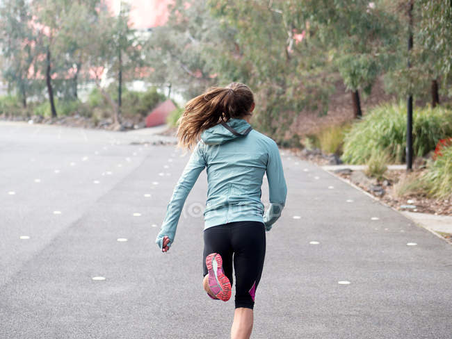 Female runner running by park — Stock Photo