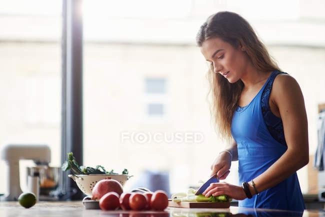 Jovem mulher na mesa da cozinha — Fotografia de Stock
