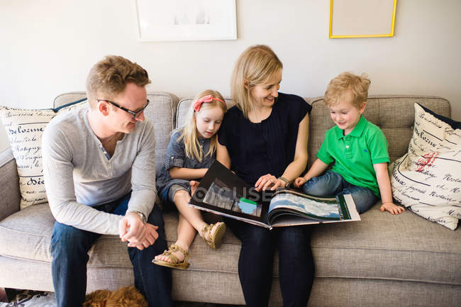 Parents on sofa reading to children — Stock Photo