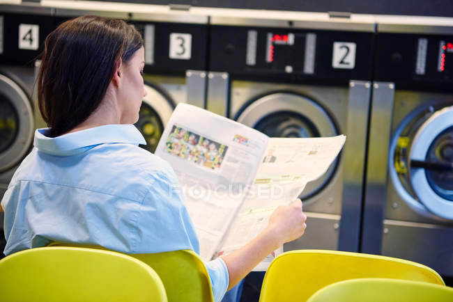 Woman reading newspaper in laundrette — Stock Photo