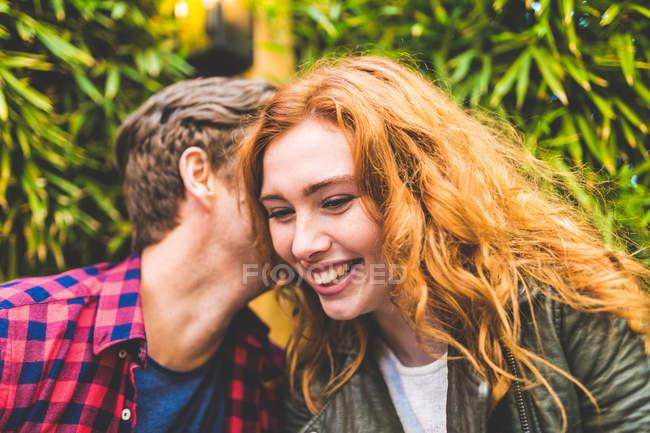 Man whispering in womans ear — Stock Photo