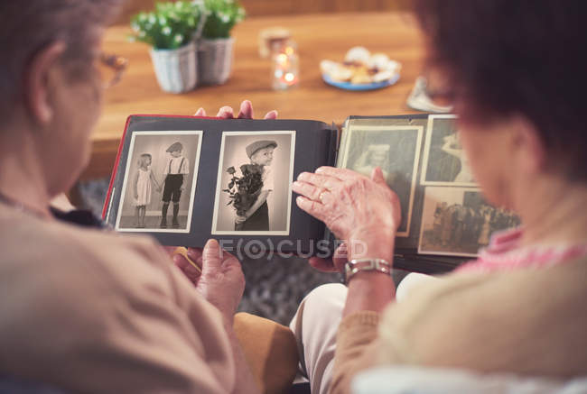 Women looking at old photograph album — Stock Photo