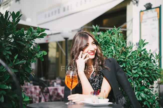 Молода жінка, сидячи за межами бару — стокове фото