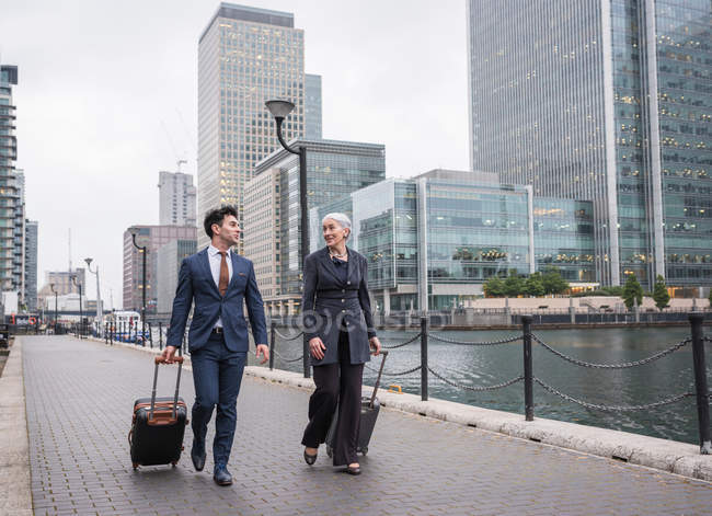 Businessman and businesswoman pulling trolley luggage — Stock Photo