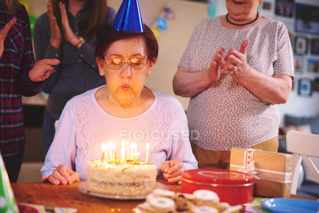Senior woman blowing out candles — Stock Photo