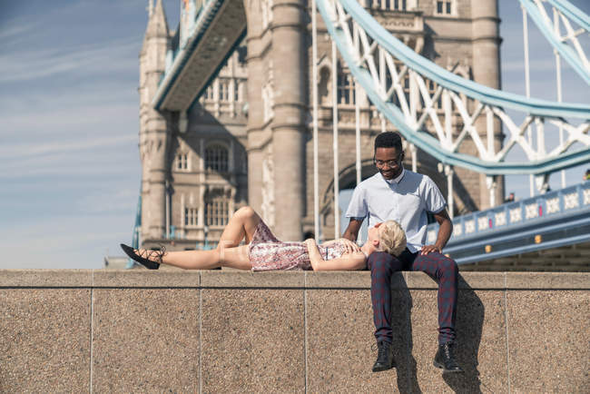 Young couple relaxing on wall — Stock Photo