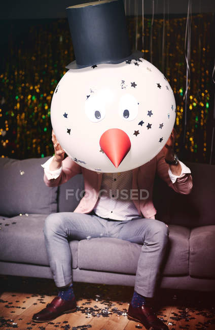 Man sitting on sofa at party — Stock Photo