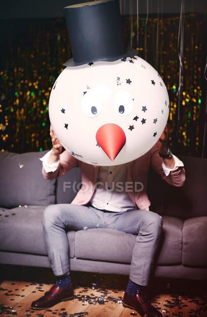 Homem sentado no sofá na festa — Fotografia de Stock
