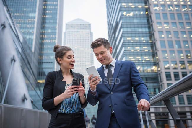 Homme d'affaires et femme d'affaires à l'aide de téléphone portable — Photo de stock