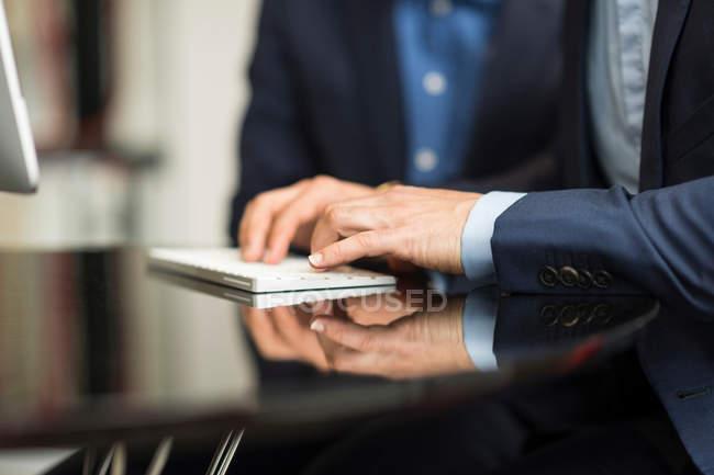 Businessman typing on desktop computer — Stock Photo