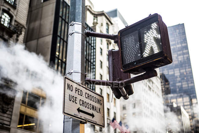 Pedestrian crossing sign and skyscrapers — Stock Photo