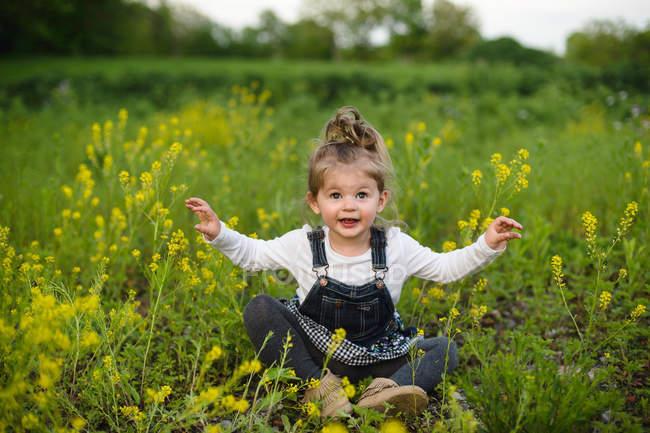 Girl cross legged in wildflower meadow — Stock Photo