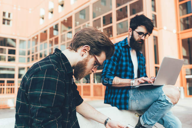 Hipsters sitting on wall typing on laptop — Stock Photo