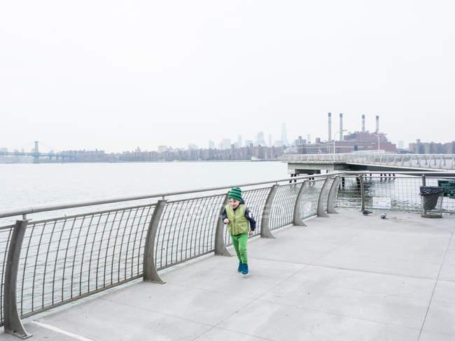Junge rennt am Ufer entlang — Stockfoto