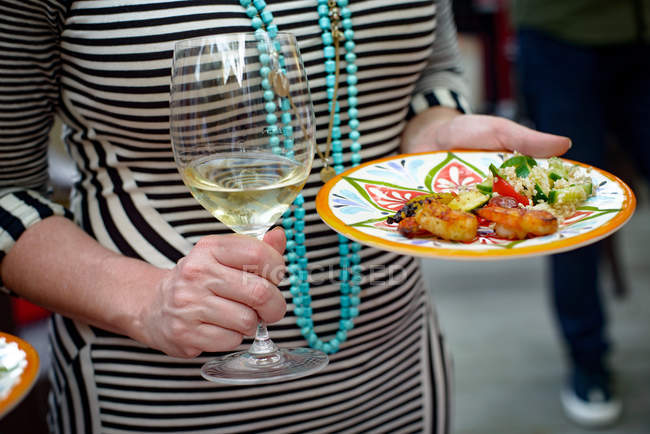 Woman holding glass of wine and plate of food — Stock Photo