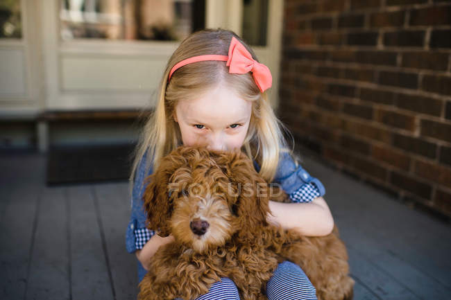 Girl kissing red haired puppy — Stock Photo