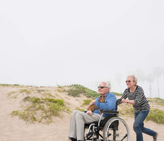 Старшая женщина толкает мужа в инвалидном кресле — стоковое фото