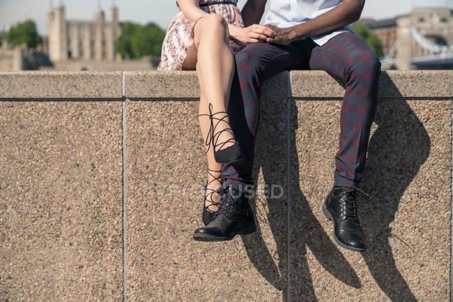 Молода пара, сидячи на стіні — стокове фото
