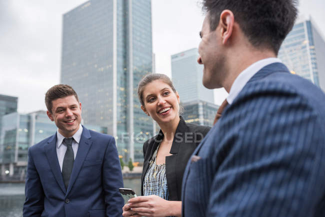 Businessmen and businesswoman in discussion outdoors — Stock Photo