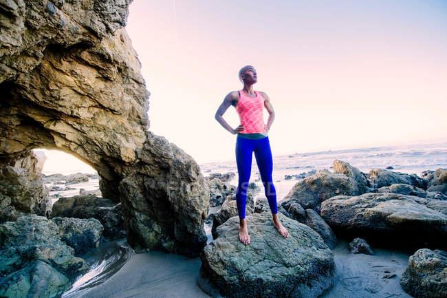 Mujer joven de pie sobre rocas - foto de stock