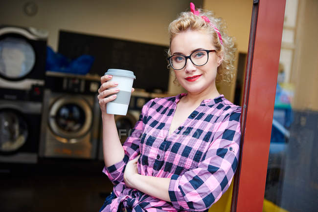 Woman leaning against laundrette door — Stock Photo