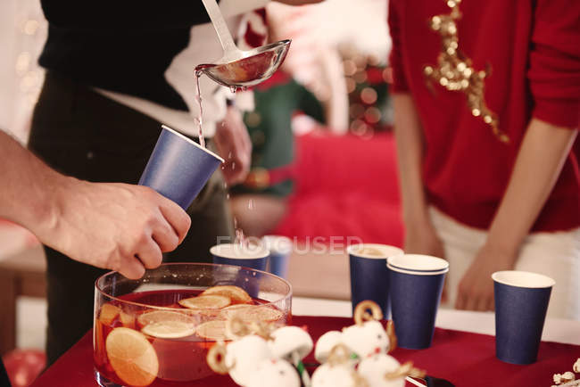 Cropped shot of young man serving punch to friends at christmas party — Stock Photo