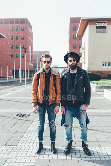 Друзья-хипстеры, стоящие в городском жилом комплексе — стоковое фото