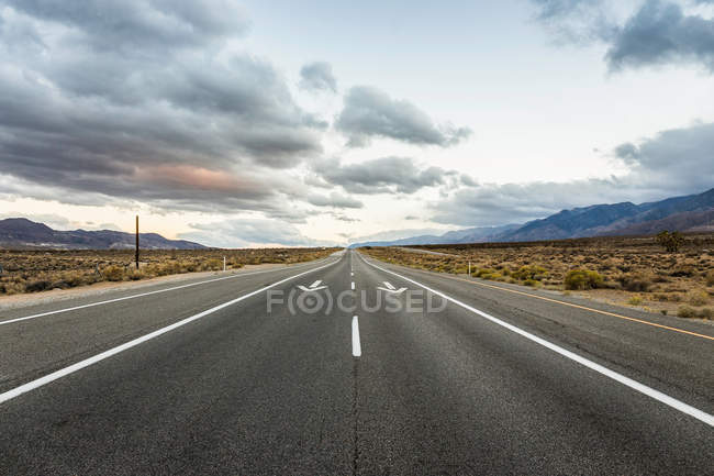 Straight road with direction arrows — Stock Photo