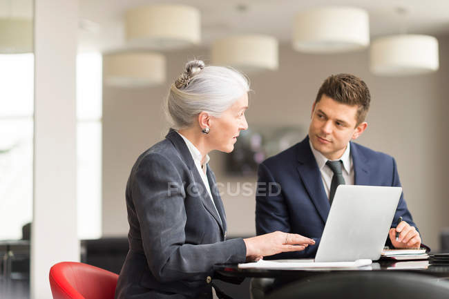 Businesswoman explaining to male colleague — Stock Photo