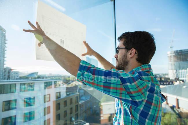 Человек, стоящий у окна офиса — стоковое фото
