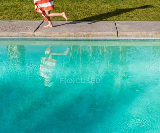 Garçon enveloppé dans la serviette de course sur le bord de la piscine — Photo de stock