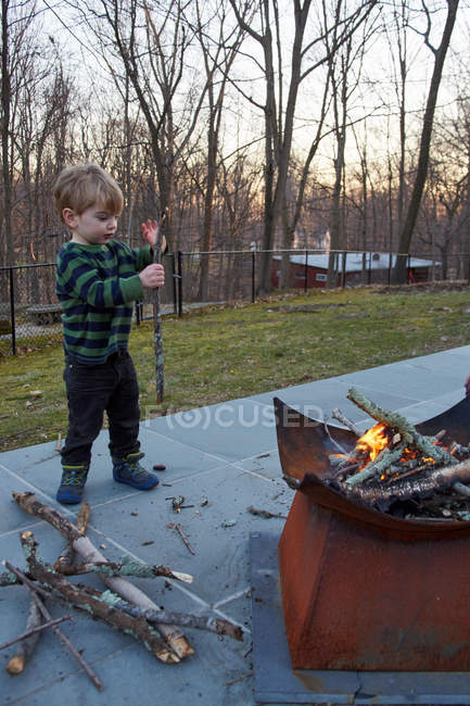 Garçon ramassant du bois pour patio — Photo de stock