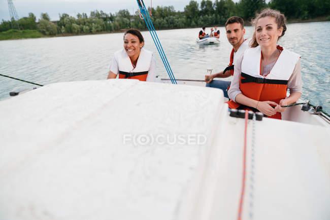 Trois amis sur le voilier — Photo de stock