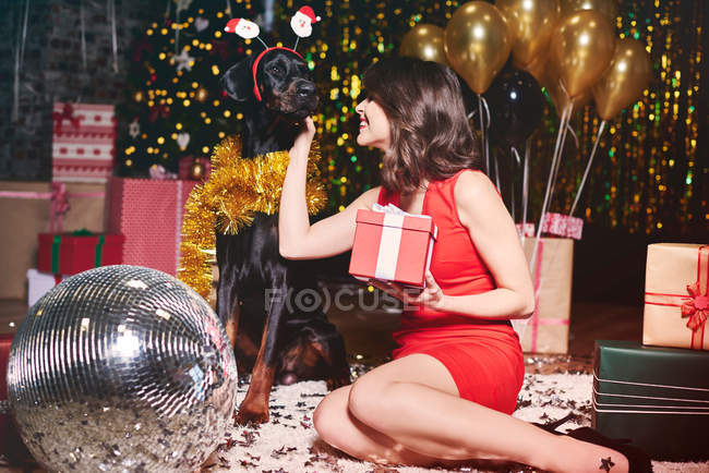 Woman stroking dog at party — Stock Photo