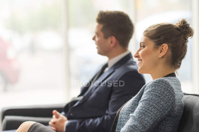 Businessman and woman sitting on sofa — Stock Photo
