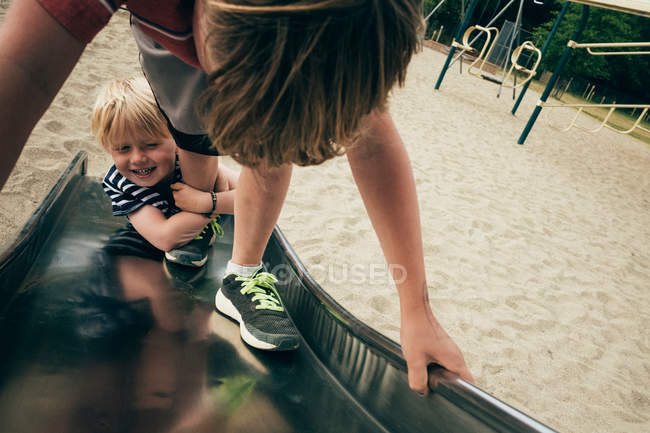 Boys playing on playground slide — Stock Photo