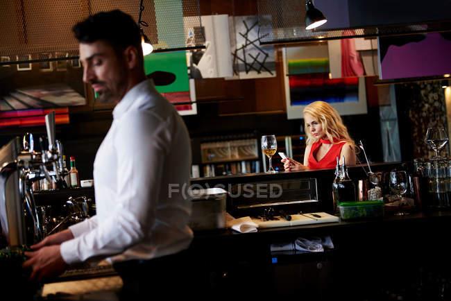 Woman sitting at bar — Stock Photo