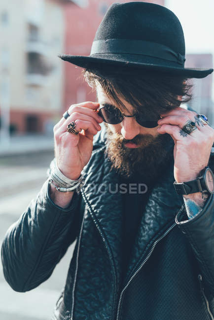 Hipster putting on sunglasses — Stock Photo