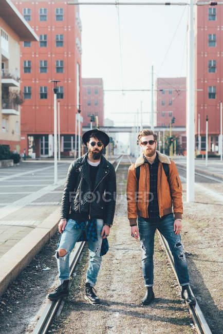 Amigos hipster de pie en las líneas de tranvía de la ciudad - foto de stock