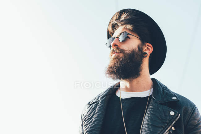 Hipster wearing sunglasses and trilby looking up — Stock Photo