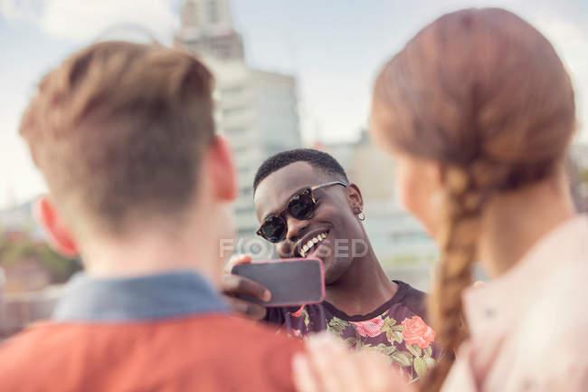 Молодой человек фотографирует друзей — стоковое фото