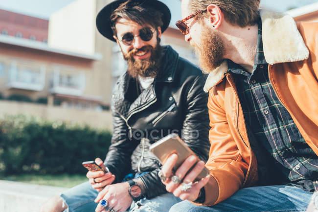 Hipsters sentados en la pared con smartphones - foto de stock