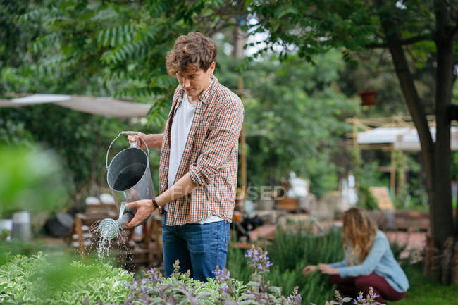 Man and woman tending to plants in urban garden — Stock Photo