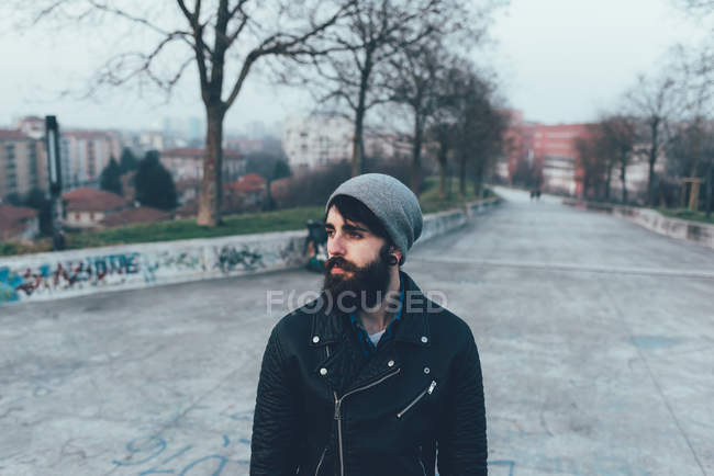 Hipster in knit hat looking away — Stock Photo