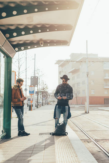 Hipsters looking at smartphones — Stock Photo