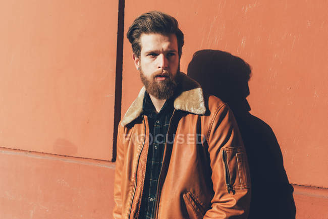 Bearded man leaning against orange wall — Stock Photo
