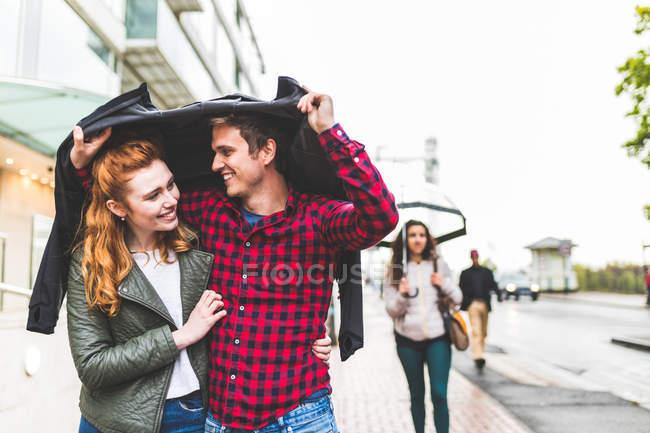 Coppia camminando all'aperto sotto la pioggia — Foto stock