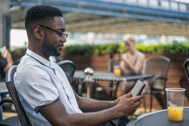 Молодий чоловік сидить надворі. — стокове фото