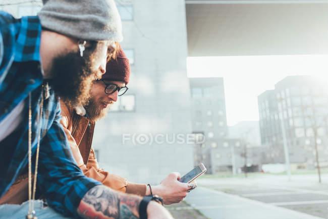 Hipster seduti sul muro guardando lo smartphone — Foto stock