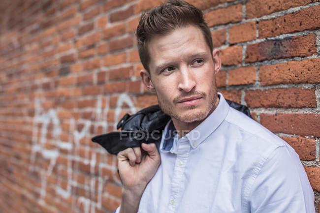 Man standing beside brick wall — Stock Photo